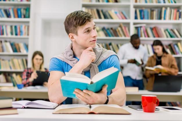 Estudante do sexo masculino bonito pensamento atraente, sentado à mesa com muitos livros e se preparando para o teste ou exame