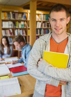 Estudante do sexo masculino com os outros em segundo plano na biblioteca