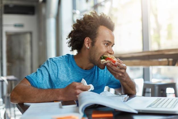 Estudante do sexo masculino de raça negra parda, ocupado estudando, descansando para comer sanduíche por minuto.