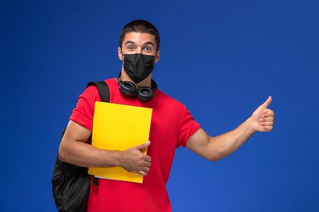 Estudante do sexo masculino de vista frontal em t-shirt vermelha usando máscara com mochila segurando arquivo amarelo sobre o fundo azul.