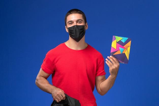 Estudante do sexo masculino de vista frontal em t-shirt vermelha usando máscara e segurando sua mochila e o caderno sobre fundo azul.