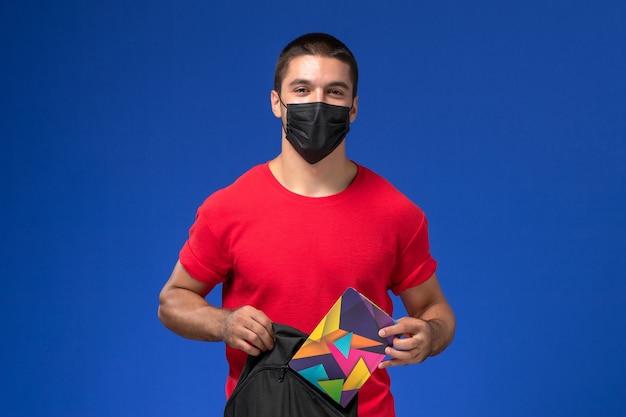 Estudante do sexo masculino de vista frontal em t-shirt vermelha usando máscara e segurando sua mochila sobre o fundo azul.