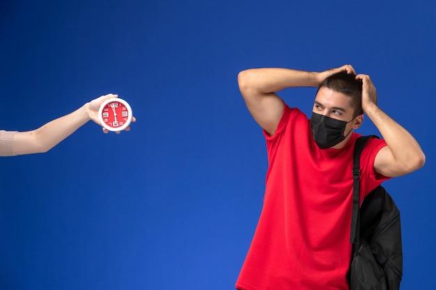 Estudante do sexo masculino de vista frontal em t-shirt vermelha usando mochila com máscara confusa sobre fundo azul.
