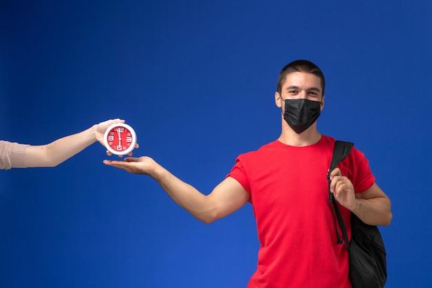 Estudante do sexo masculino de vista frontal em t-shirt vermelha usando mochila com máscara posando sobre a mesa azul.