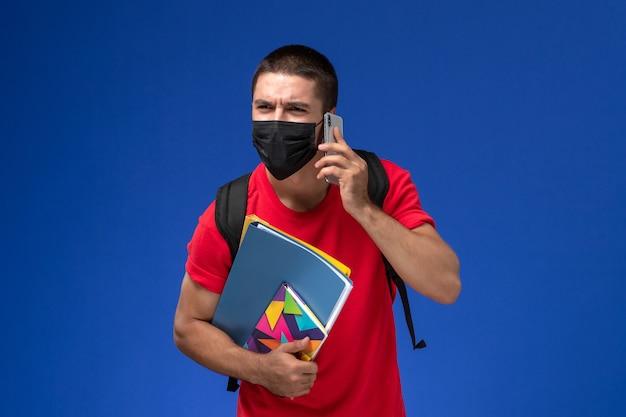 Estudante do sexo masculino de vista frontal em t-shirt vermelha usando mochila com máscara segurando arquivos de caderno, falando ao telefone na mesa azul.