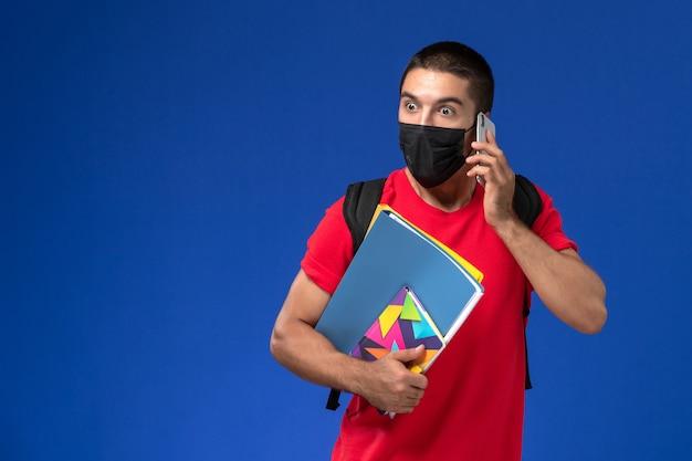 Estudante do sexo masculino de vista frontal em t-shirt vermelha usando mochila com máscara segurando arquivos de caderno, falando ao telefone sobre o fundo azul.
