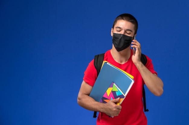 Estudante do sexo masculino de vista frontal em t-shirt vermelha usando mochila com máscara segurando arquivos e falando ao telefone sobre fundo azul.