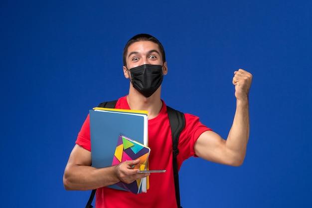 Estudante do sexo masculino de vista frontal em t-shirt vermelha usando mochila com máscara segurando arquivos e usando o telefone regozijando-se na mesa azul.