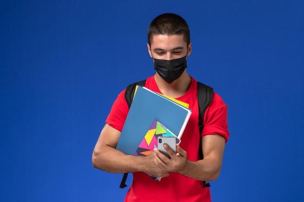 Estudante do sexo masculino de vista frontal em t-shirt vermelha usando mochila com máscara segurando arquivos e usando o telefone sobre fundo azul.