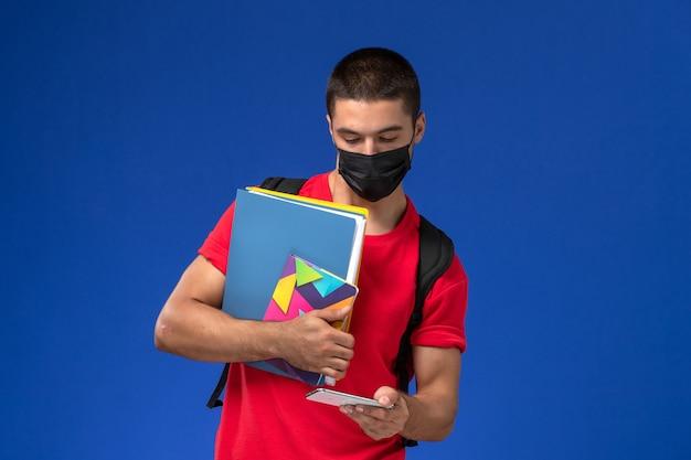 Estudante do sexo masculino de vista frontal em t-shirt vermelha usando mochila com máscara segurando arquivos e usando seu telefone sobre o fundo azul.