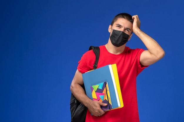 Estudante do sexo masculino de vista frontal em t-shirt vermelha, usando mochila em máscara estéril preta segurando cadernos na mesa azul.