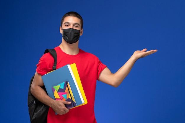 Estudante do sexo masculino de vista frontal em t-shirt vermelha, usando mochila em máscara estéril preta segurando cadernos sobre o fundo azul.