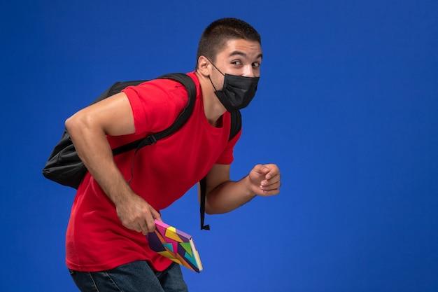 Estudante do sexo masculino de vista frontal em t-shirt vermelha, usando mochila em máscara estéril preta segurando caneta e caderno em execução na mesa azul.