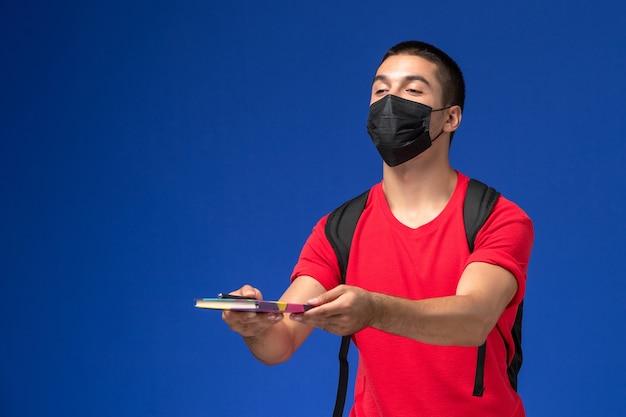 Estudante do sexo masculino de vista frontal em t-shirt vermelha usando mochila em máscara estéril preta segurando caneta e caderno na mesa azul.