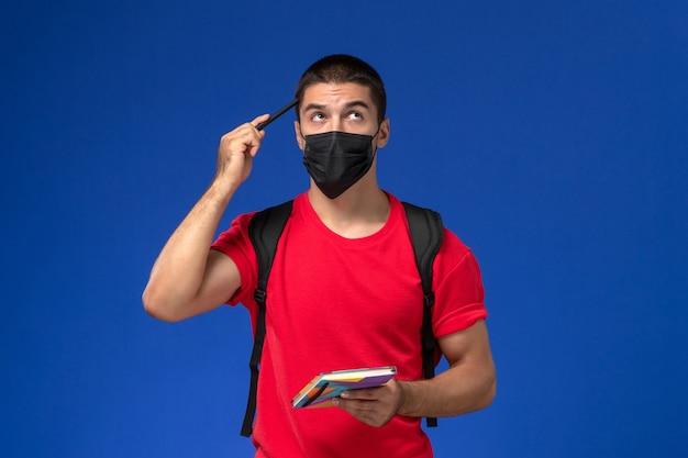 Estudante do sexo masculino de vista frontal em t-shirt vermelha, usando mochila em máscara estéril preta segurando caneta e caderno pensando sobre fundo azul.