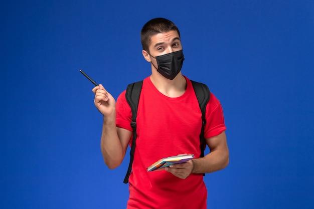 Estudante do sexo masculino de vista frontal em t-shirt vermelha, usando mochila em máscara estéril preta segurando caneta e caderno sobre fundo azul.