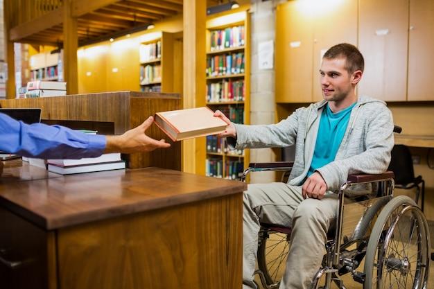 Estudante do sexo masculino em cadeira de rodas no balcão da biblioteca da faculdade