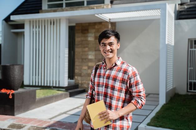 Estudante do sexo masculino em pé na frente de sua casa