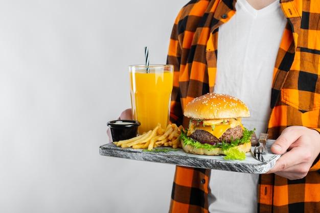 Estudante do sexo masculino está segurando placa com um hambúrguer fresco.