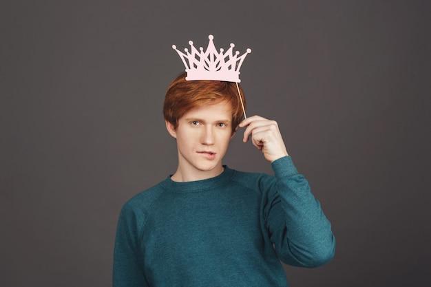 Estudante do sexo masculino jovem atraente ruiva sexy camisola verde aconchegante segurando a coroa de papel sob a cabeça, mordendo os lábios, com flerte e expressão relaxada. parede escura