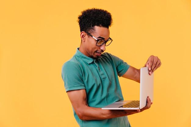 Estudante do sexo masculino negro usando o computador para o trabalho. retrato de freelancer concentrado em copos.