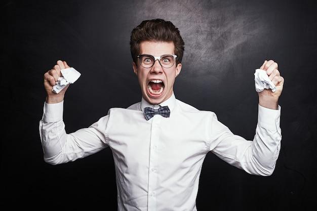 Estudante do sexo masculino nerd furioso com roupas elegantes e óculos amassando papéis com dever de casa e gritando de raiva