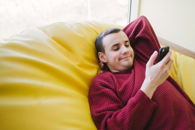 Estudante do sexo masculino novo positivo que encontra-se e que olha seu smartphone. depois de aprender em uma cadeira confortável. retrato interior