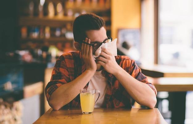 Estudante doente assoando o nariz em um lenço de papel.