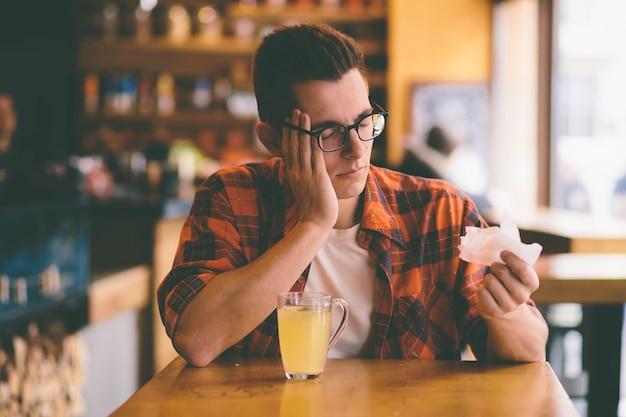 Estudante doente assoando o nariz em um lenço de papel