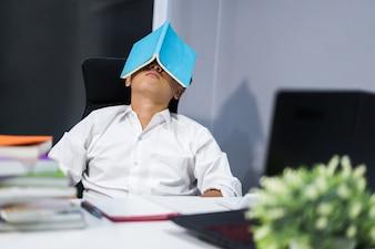 Estudante dormindo na mesa com um livro no rosto