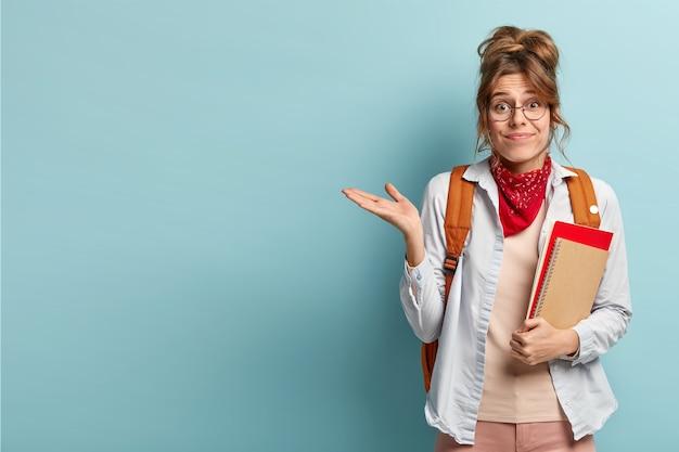 Estudante duvidosa e inconsciente levanta a palma da mão, segura um bloco de notas em espiral, carrega uma mochila, gesticula sobre o espaço em branco azul