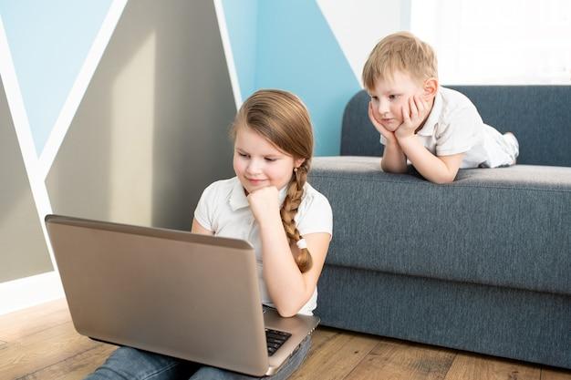 Estudante e garota estudando em casa com o notebook laptop digital e fazendo lição de casa da escola.