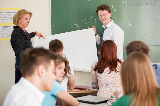 Estudante e professor com um painel
