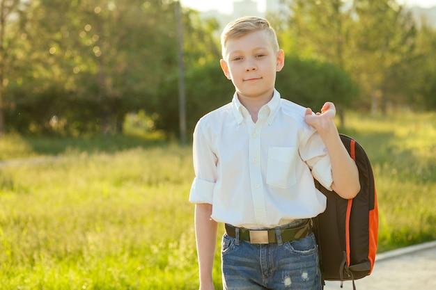Estudante elegante e jovem em uma camisa branca e calça jeans com uma mochila no parque para a escola.