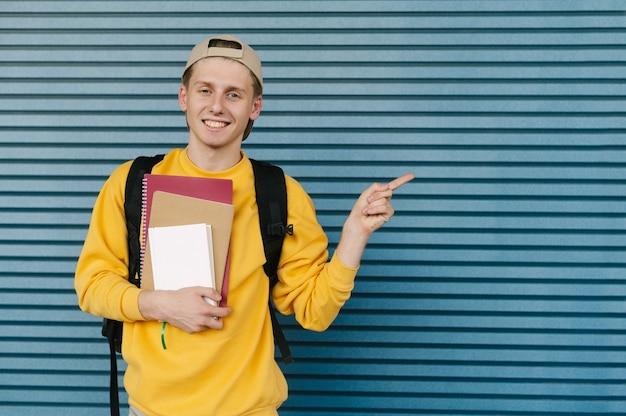 Estudante elegante sorridente com livros e cadernos nas mãos está de pé