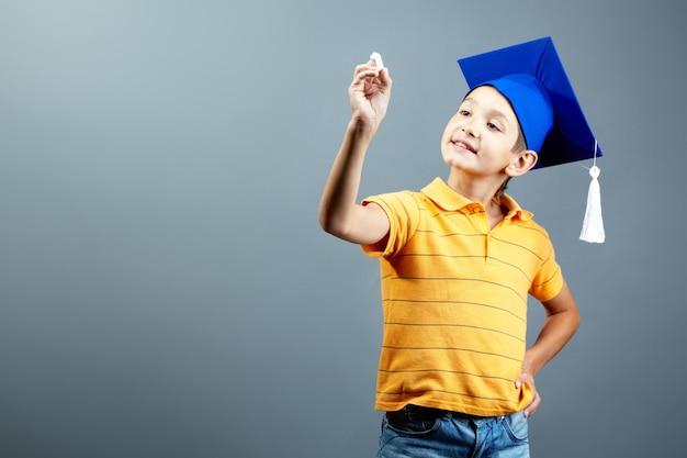 Estudante elementar com um tampão da graduação e um giz