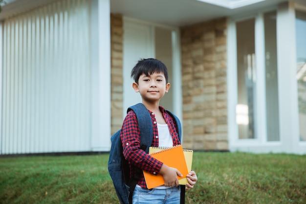 Estudante elementar na frente de sua casa, sorrindo com mochila