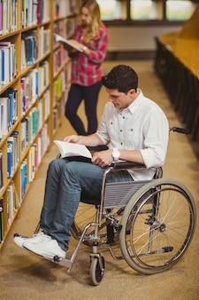 Estudante em cadeira de rodas, conversando com o colega na biblioteca