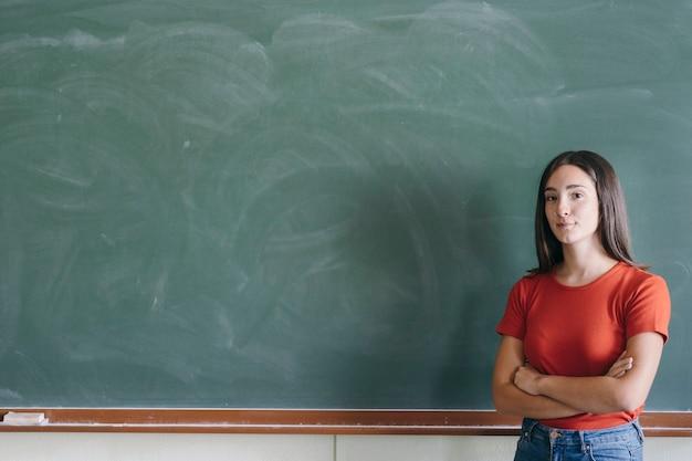 Estudante em frente ao quadro-negro com braços cruzados