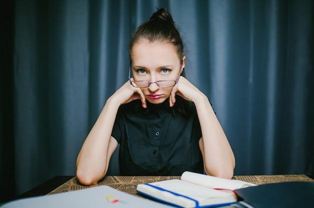Estudante em óculos sentado em uma mesa em casa