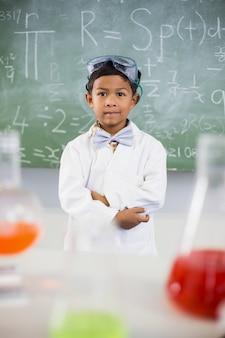 Estudante em pé na sala de aula com balão de químico em primeiro plano