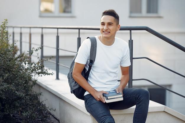 Estudante em um campus universitário com livros