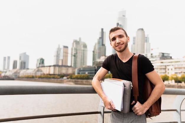 Estudante em uma cidade grande, segurando suas anotações