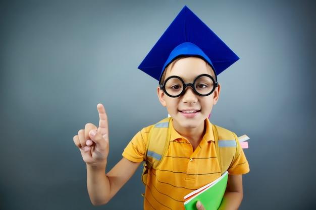 Estudante encantador com tampão azul da graduação
