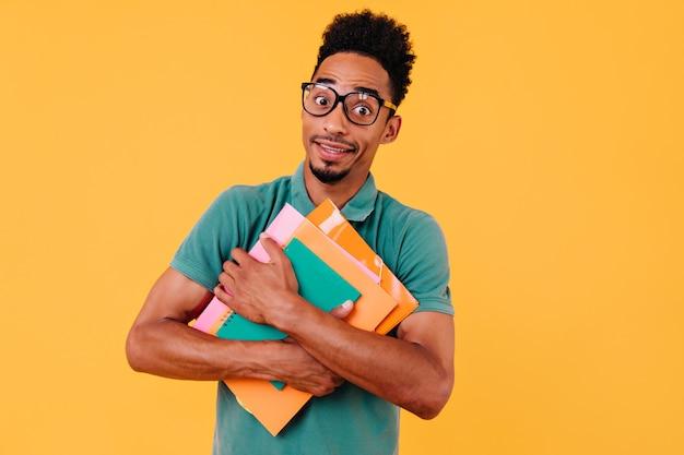 Estudante encaracolado espantado fazendo caretas engraçadas. jovem inteligente de óculos segurando livros.