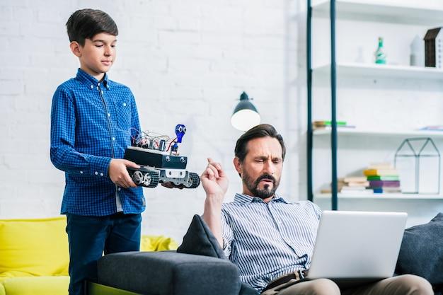 Estudante engenhoso segurando um robô enquanto seu pai ocupado trabalha online