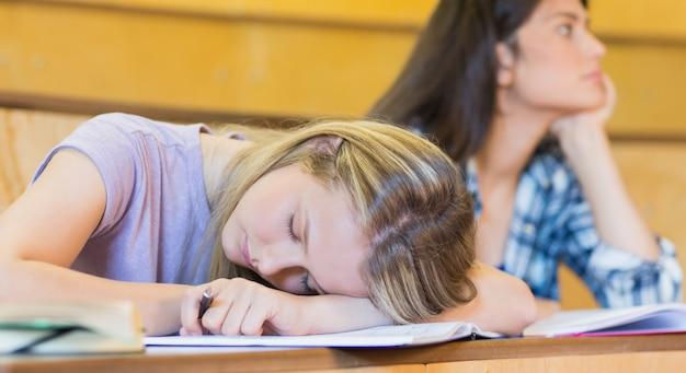 Estudante entediado ouvindo enquanto colega dormindo na universidade