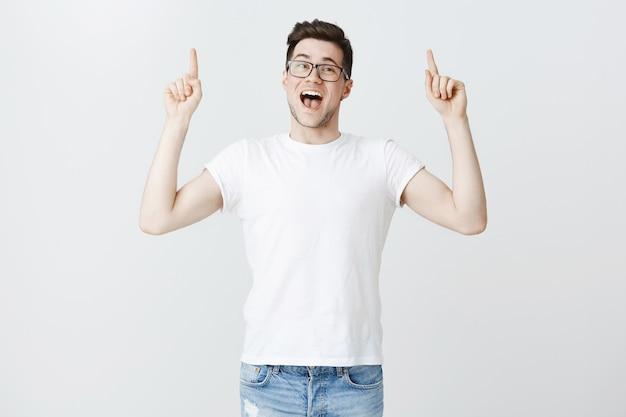 Estudante entusiasta de óculos, convidando para eventos, apontando o dedo para cima