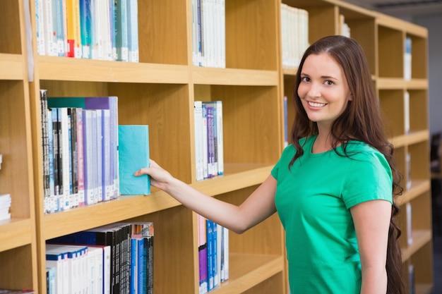 Estudante escolhendo um livro da prateleira na biblioteca