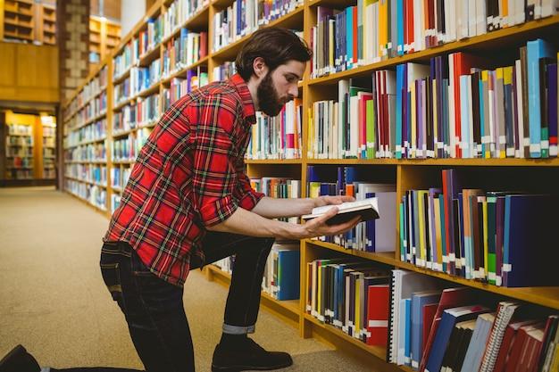 Estudante, escolhendo um livro da prateleira na biblioteca